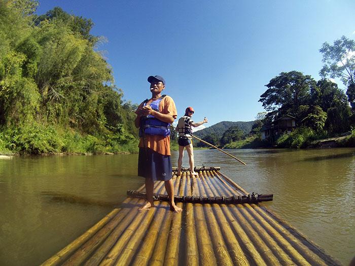 L'instructeur laisse les touristes diriger le bamboo raft
